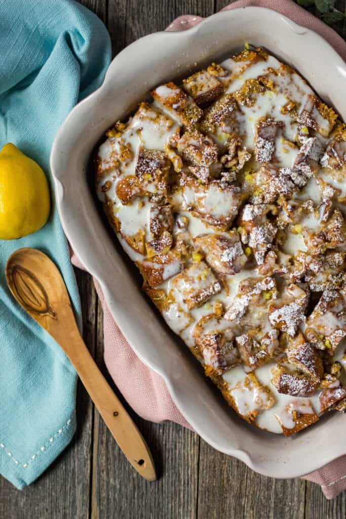 overhead shot of lemon bread pudding with greek yogurt glaze on wooden surface with wooden spoon and lemon in perimeter of shot
