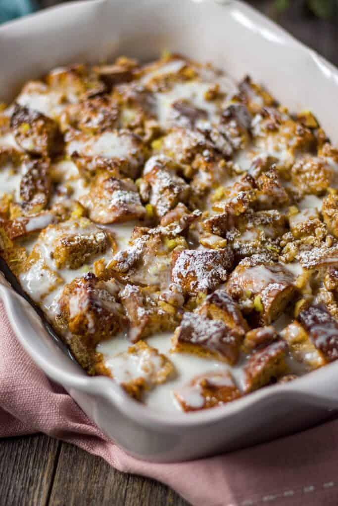 side shot of lemon bread pudding with lemon greek yogurt glazein glass baking dish on wooden surface.