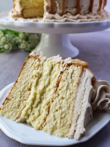 close up of slice of caramel cheesecake layer cake