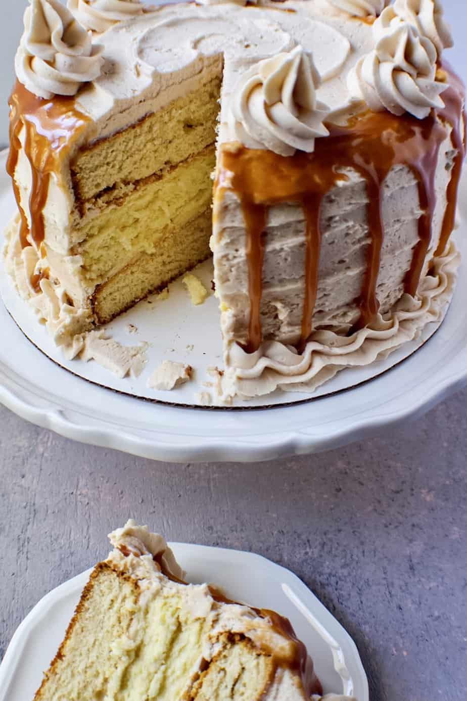 close up of slice caramel cheesecake layer cake on white cake stand.