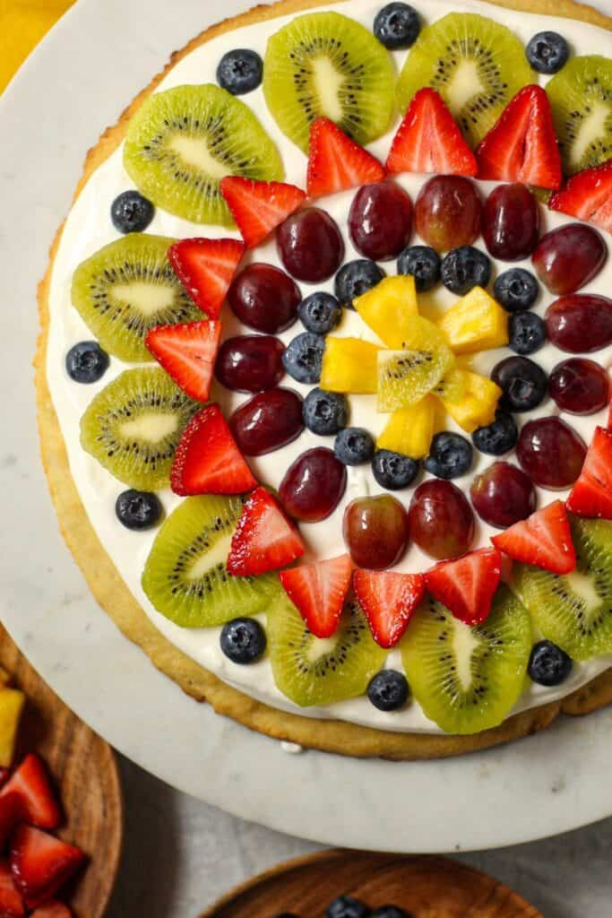 overhead shot of gluten=free fruit pizza on cake stand