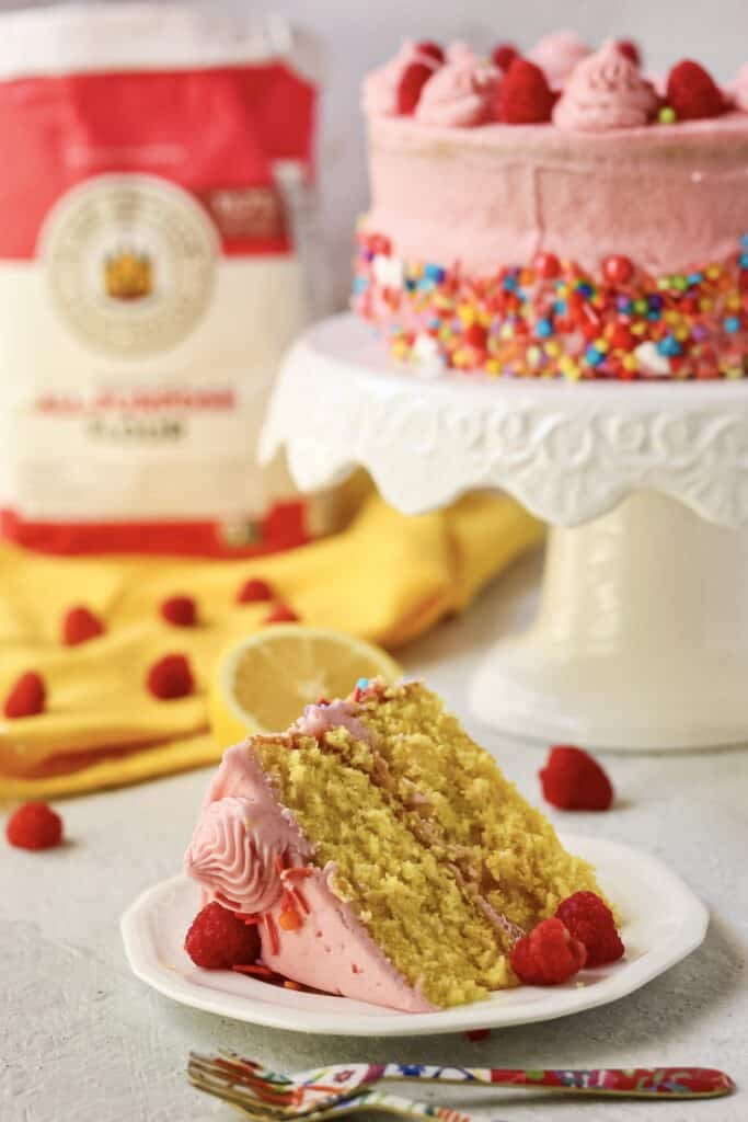 side shot of lemon raspberry birthday cake on cake stand with bag of flour in the background