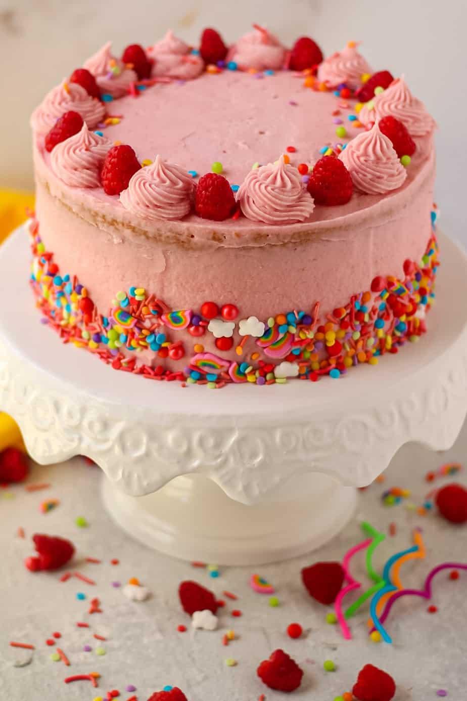 side shot of lemon raspberry birthday cake on white cake stand