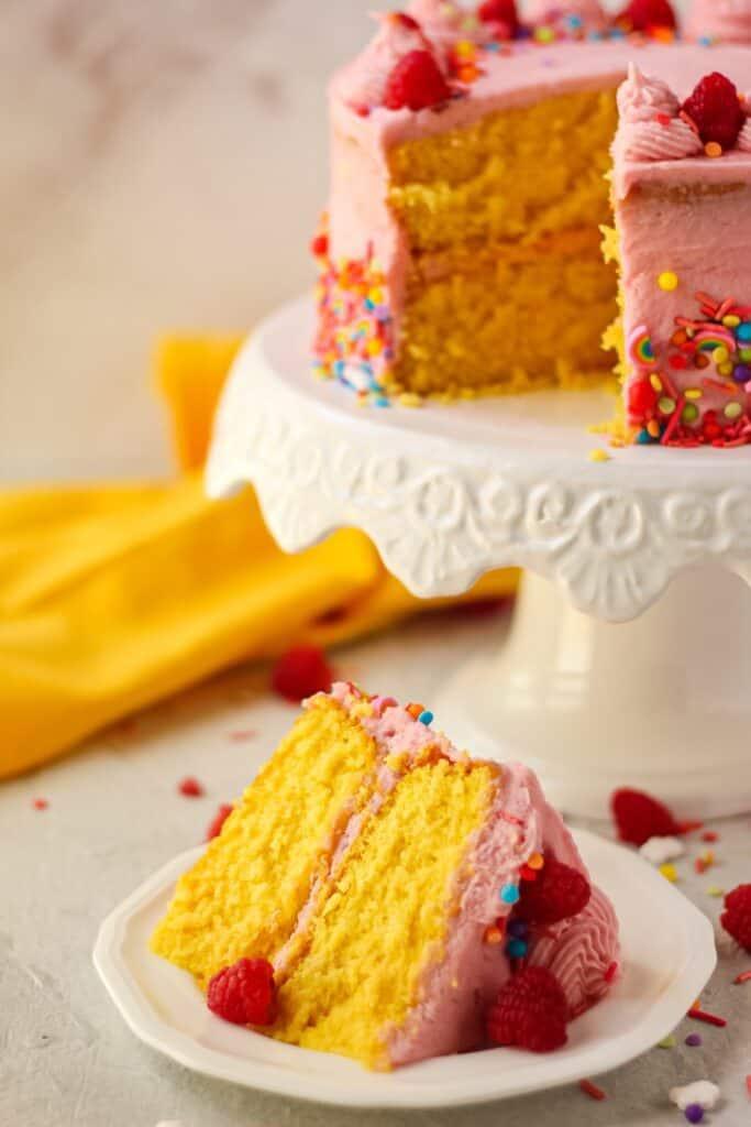 side shot of sliced lemon raspberry birthday cake on white plate