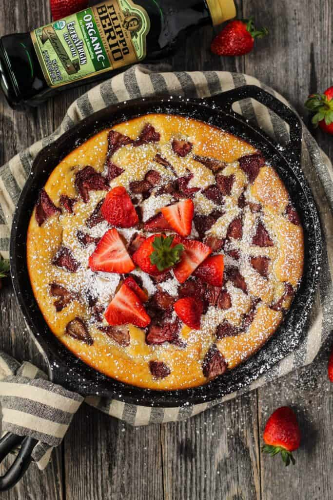 overhead shot of roasted strawberry olive oil skillet cake on wooden surface