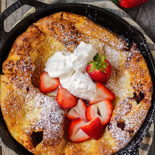 overhead shot of roasted strawberry dutch baby in cast iron skillet on wooden surface