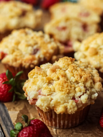 side shot of strawberry crumble muffins on parchment paper