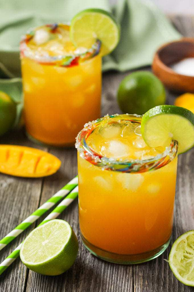side angle shot of virgin mango margaritas on wooden surface in clear glasses