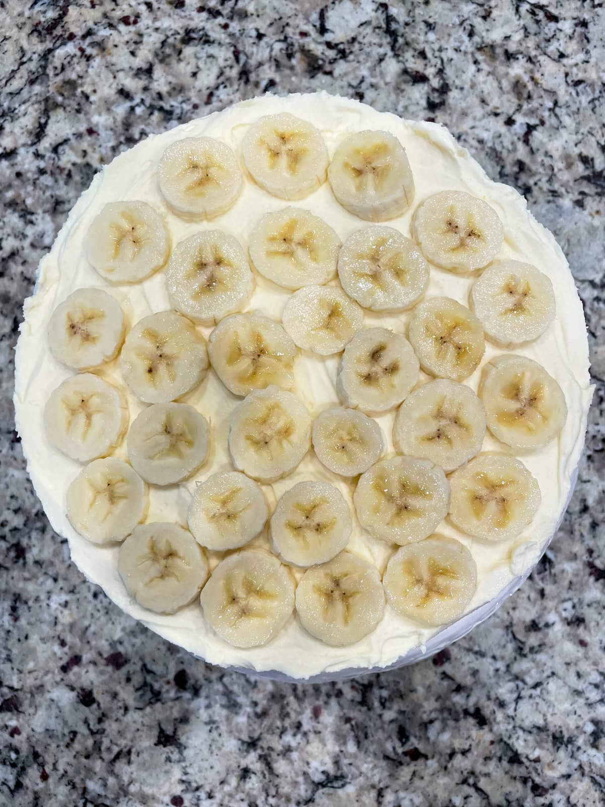 overhead shot of banana slice layer on top of banana icebox pie on granite countertop