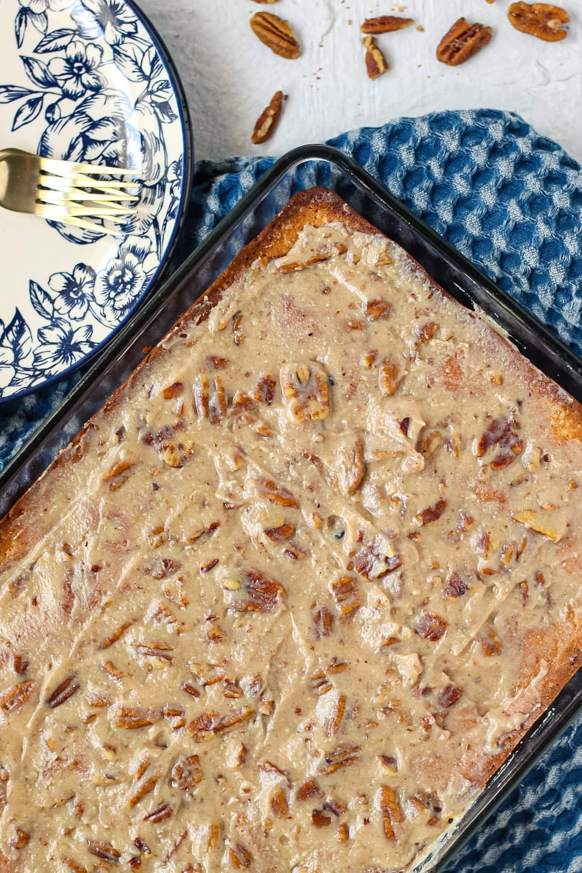 overhead shot of praline poke cake in glass baking dish with blue dish towel underneath.