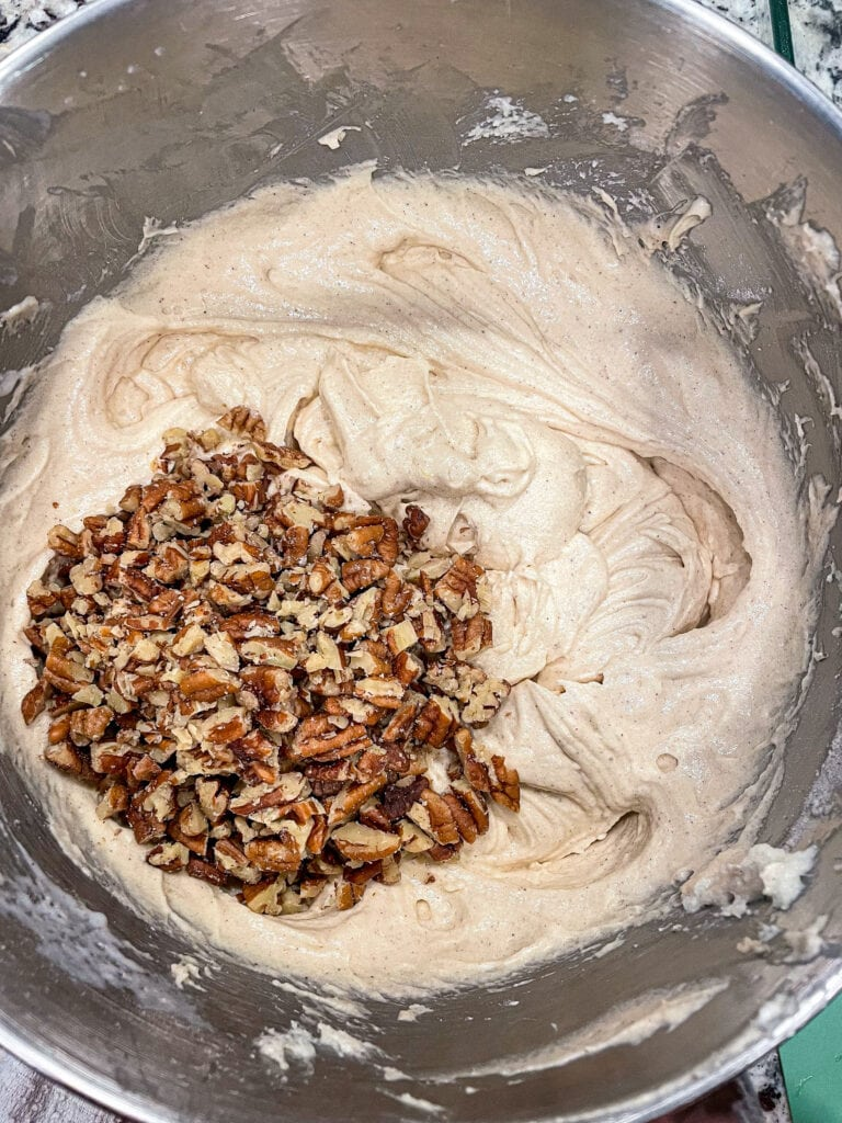 overhead shot of praline cake batter in a mixing bowl with pecans.