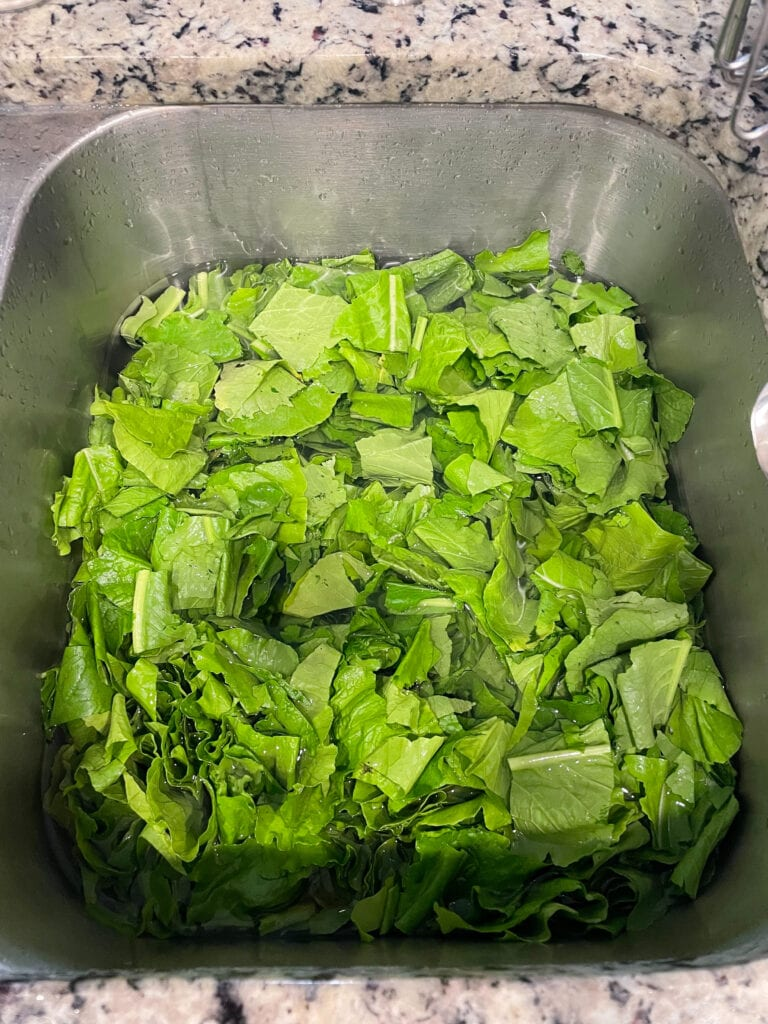 chopped turnip greens being cleaned in a kitchen sink.