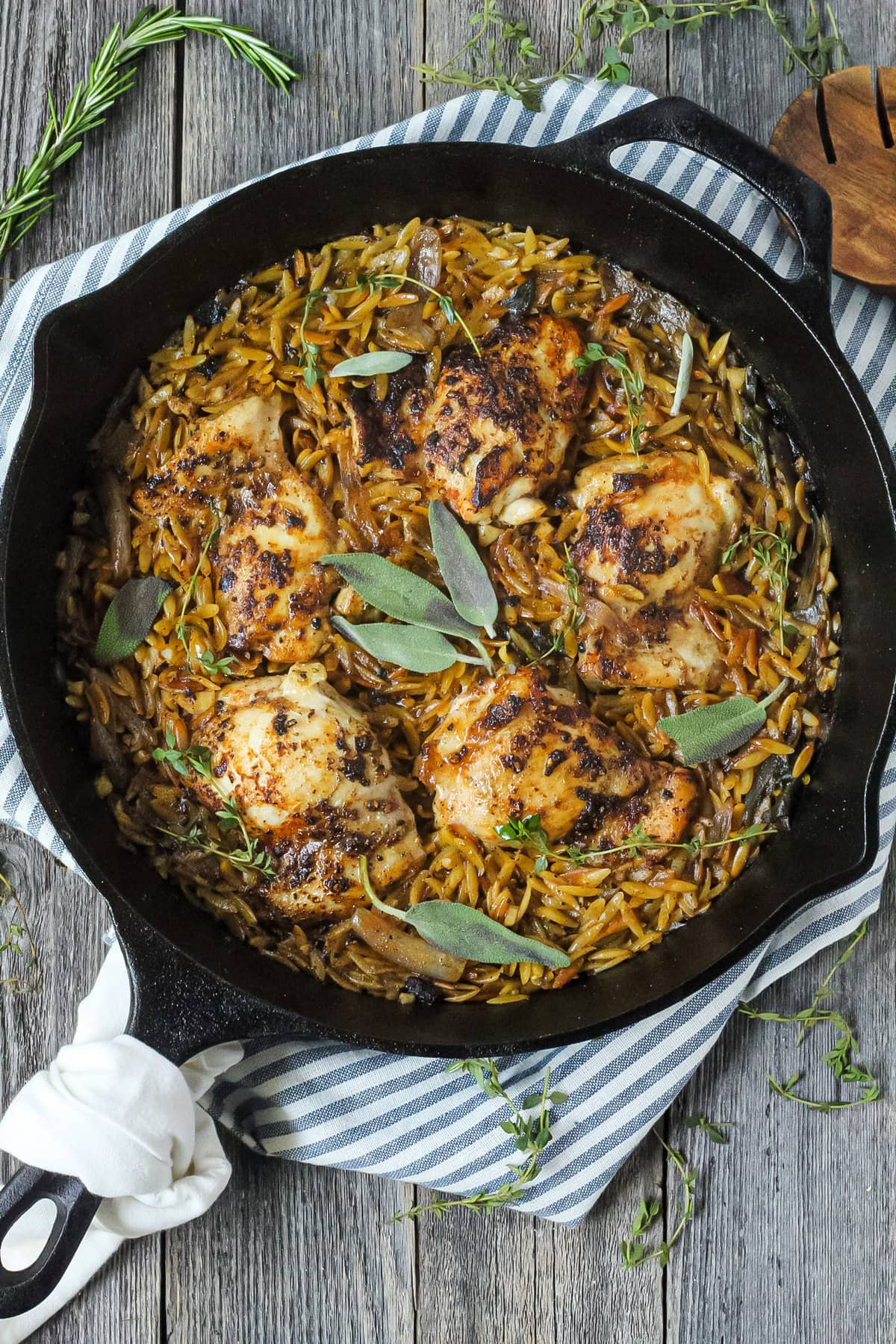 overhead shot of one pan sage butter chicken and orzo in a cast iron skillet on wooden surface