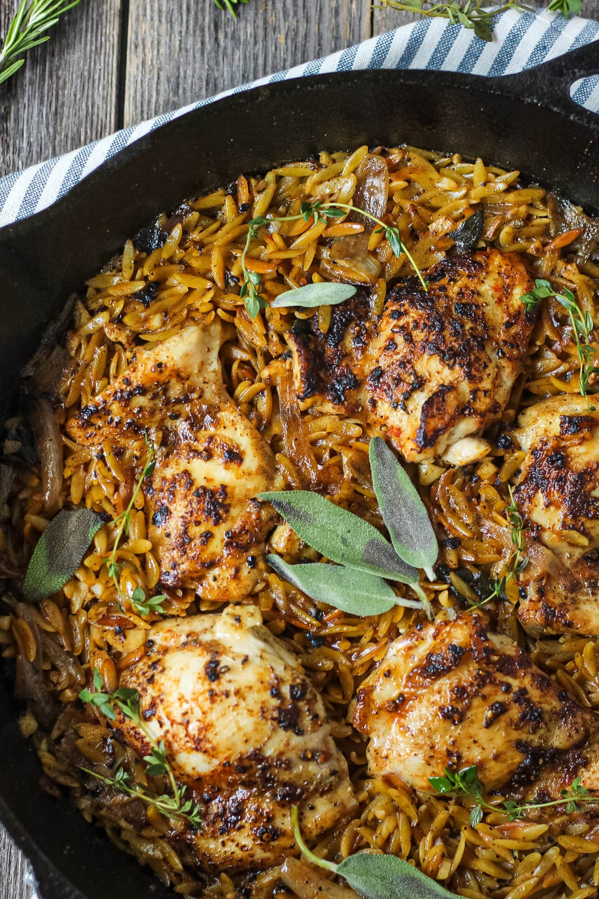 overhead close up shot of one pan sage butter chicken and orzo in a cast iron skillet on wooden surface