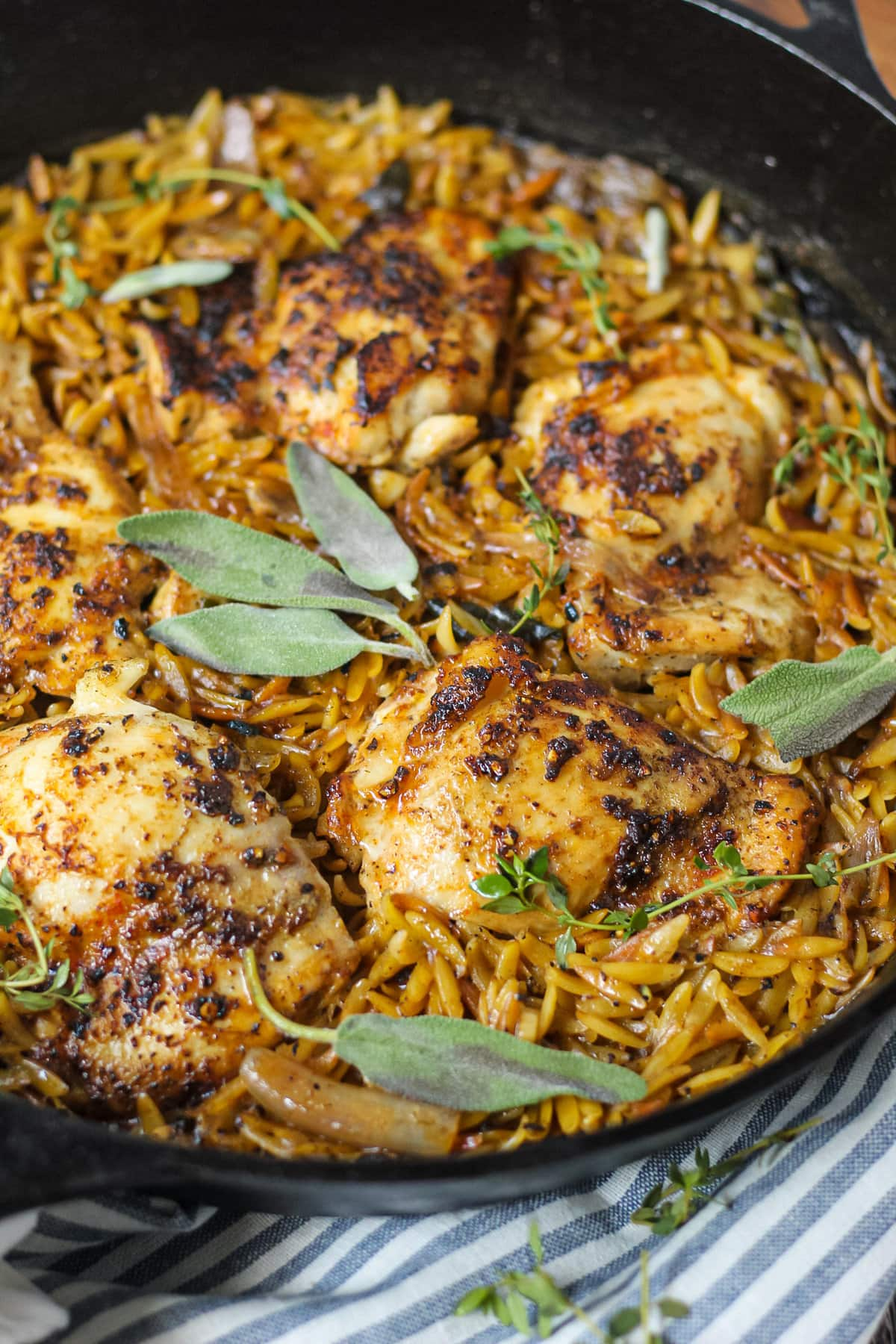 close up side angle shot of one pan sage butter chicken and orzo in a cast iron skillet on wooden surface