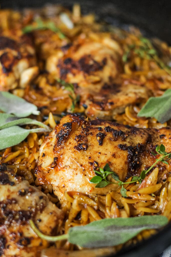 detailed shot of one pan sage butter chicken and orzo in a cast iron skillet on wooden surface