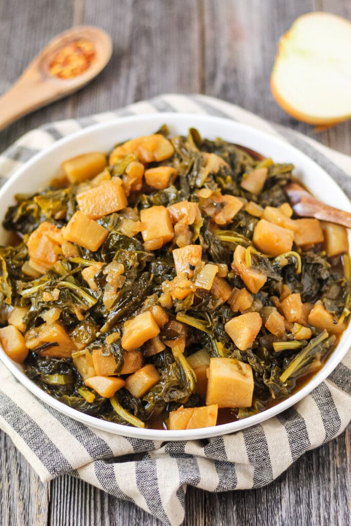 side angle shot of sweet and spicy turnip greens in white bowl on wooden surface.