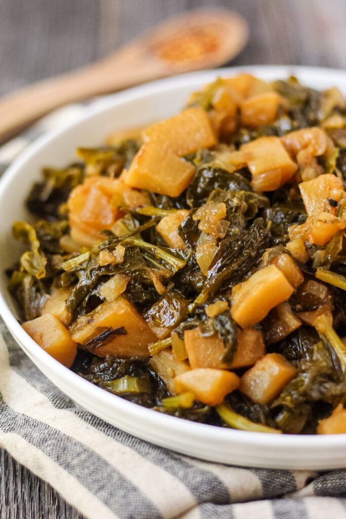 close up shot of sweet and spicy turnip greens in white bowl on wooden surface.