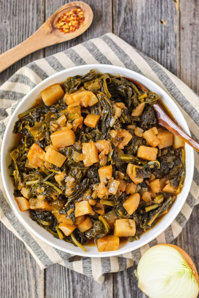 overhead shot of sweet and spicy turnip greens in white bowl on wooden surface.