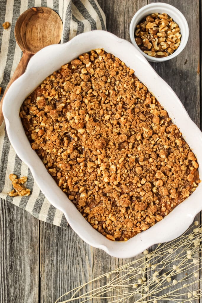 overhead shot of maple walnut sweet potato casserole in a glass baking dish on top of a wooden surface. Striped dish towel underneath dish and wooden spoon in the top left hand corner.