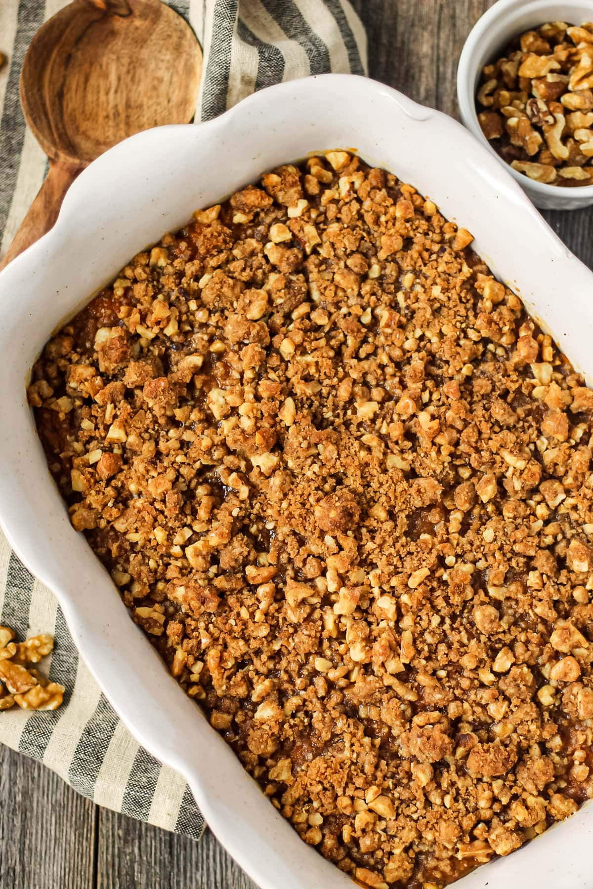 overhead shot of maple walnut sweet potato casserole in a glass baking dish on top of a wooden surface. Striped dish towel underneath dish and wooden spoon in left hand corner.