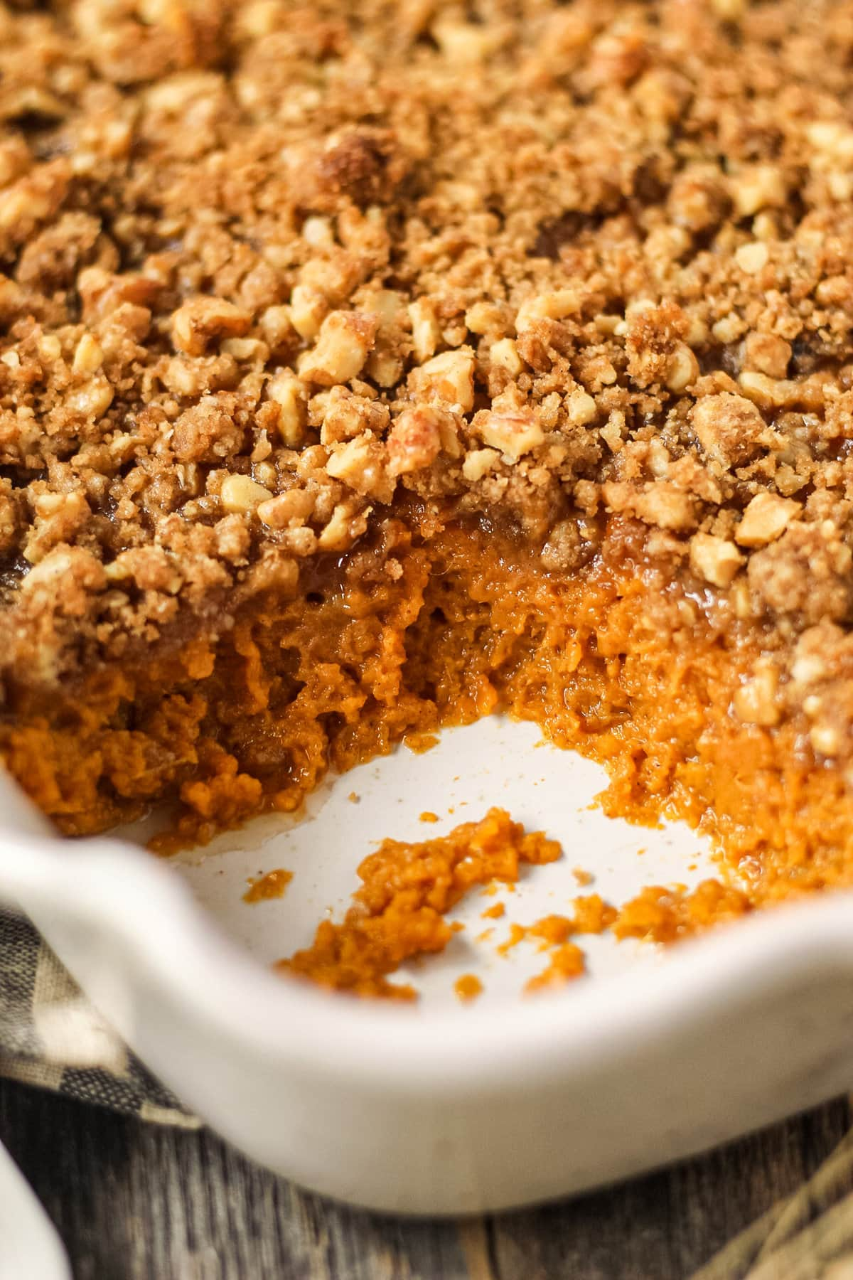 close up shot of maple walnut sweet potato casserole section wher a serving has been removed.