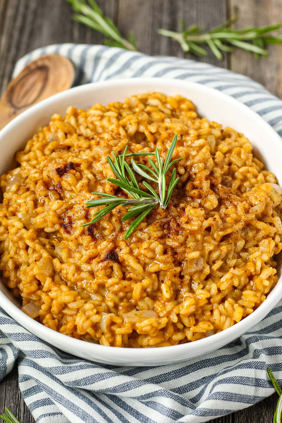 side angle shot of creamy pumpkin risotto in a white serving bowl with a striped linen underneath and a wooden serving spoon in the top left corner.