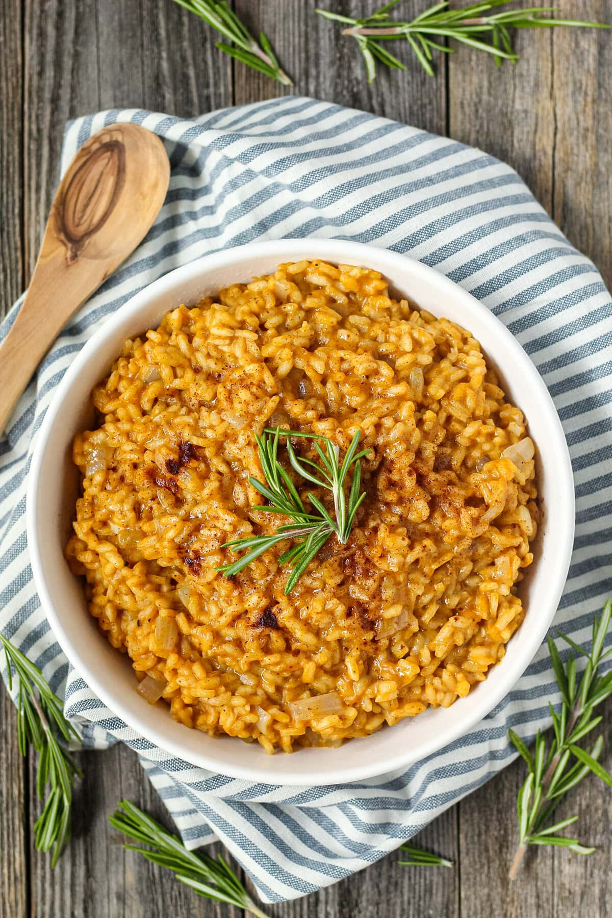 overhead shot of creamy pumpkin risotto in a white serving bowl with a striped linen underneath and a wooden serving spoon in the top left corner.