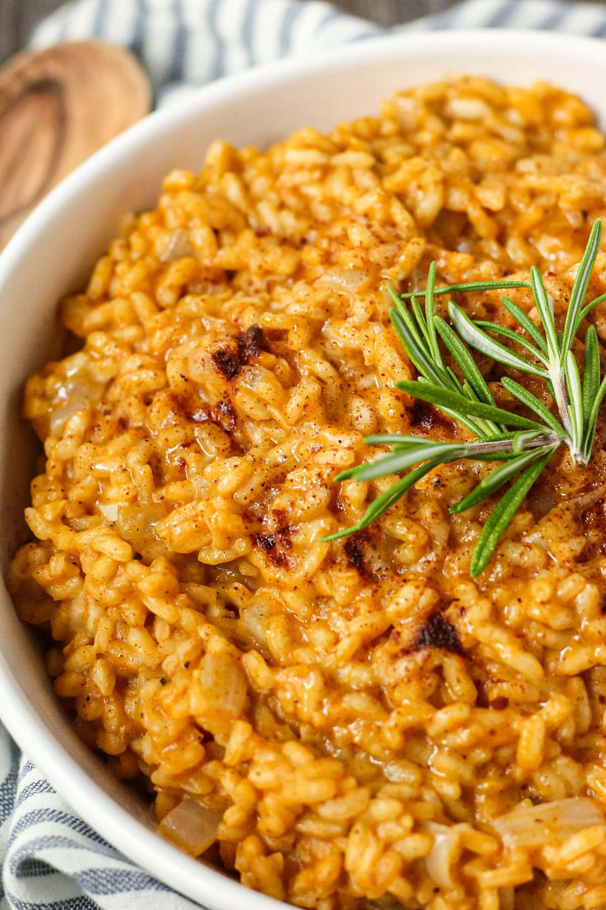 close up side angle shot of creamy pumpkin risotto in a white serving bowl with a striped linen underneath and a wooden serving spoon in the top left corner.