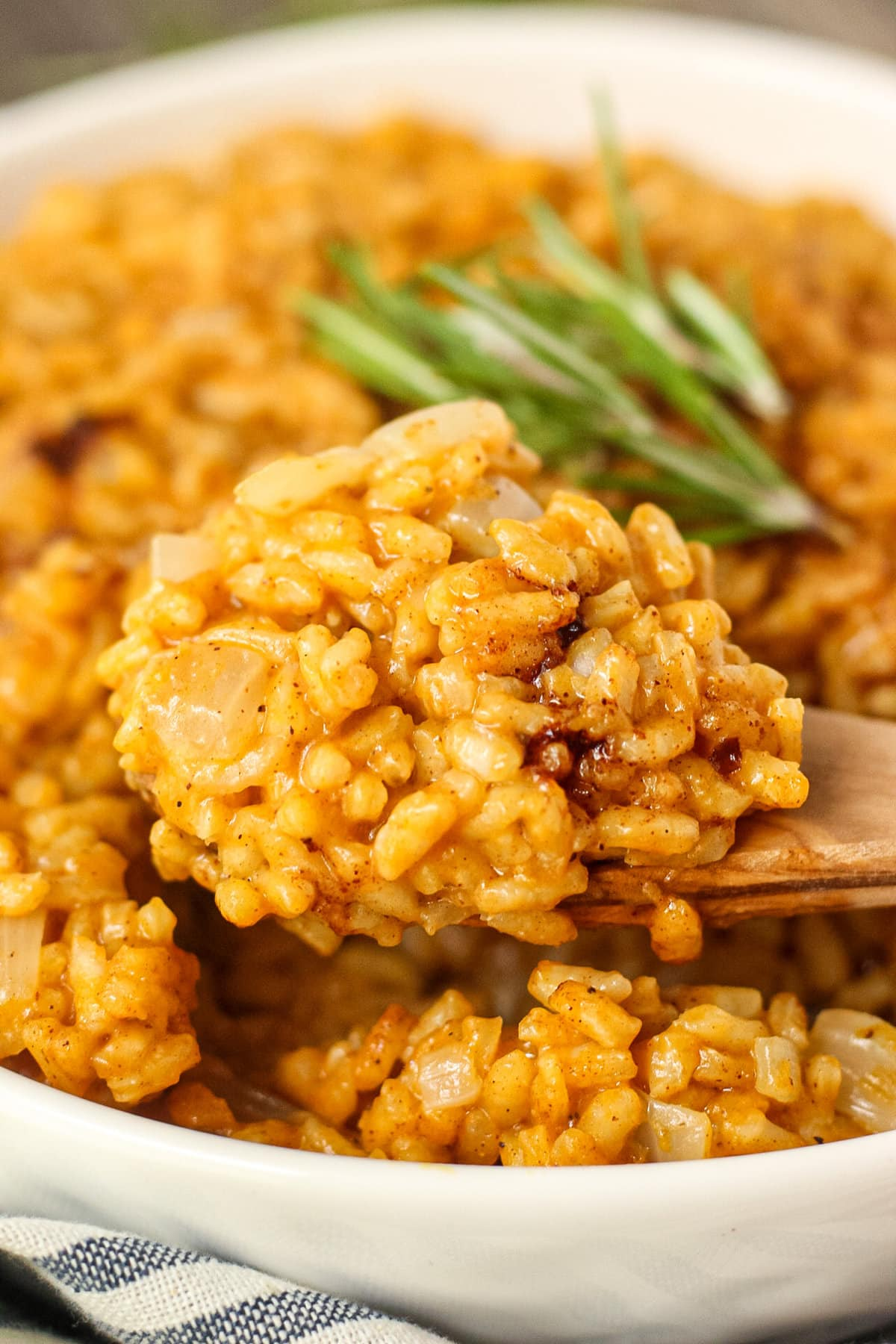 close up side angle shot of creamy pumpkin risotto on a wooden spoon in the forefront with more risotto in a white serving bowl with a striped linen underneath in the background.