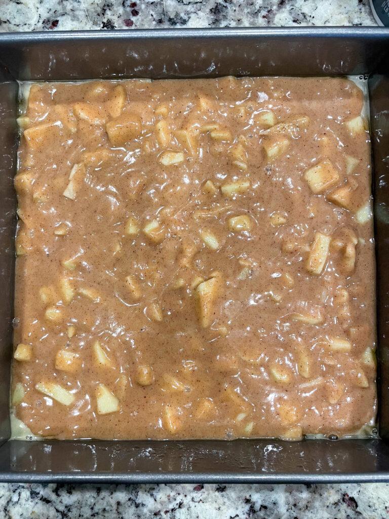 apple crumb cake batter in pan before baking.