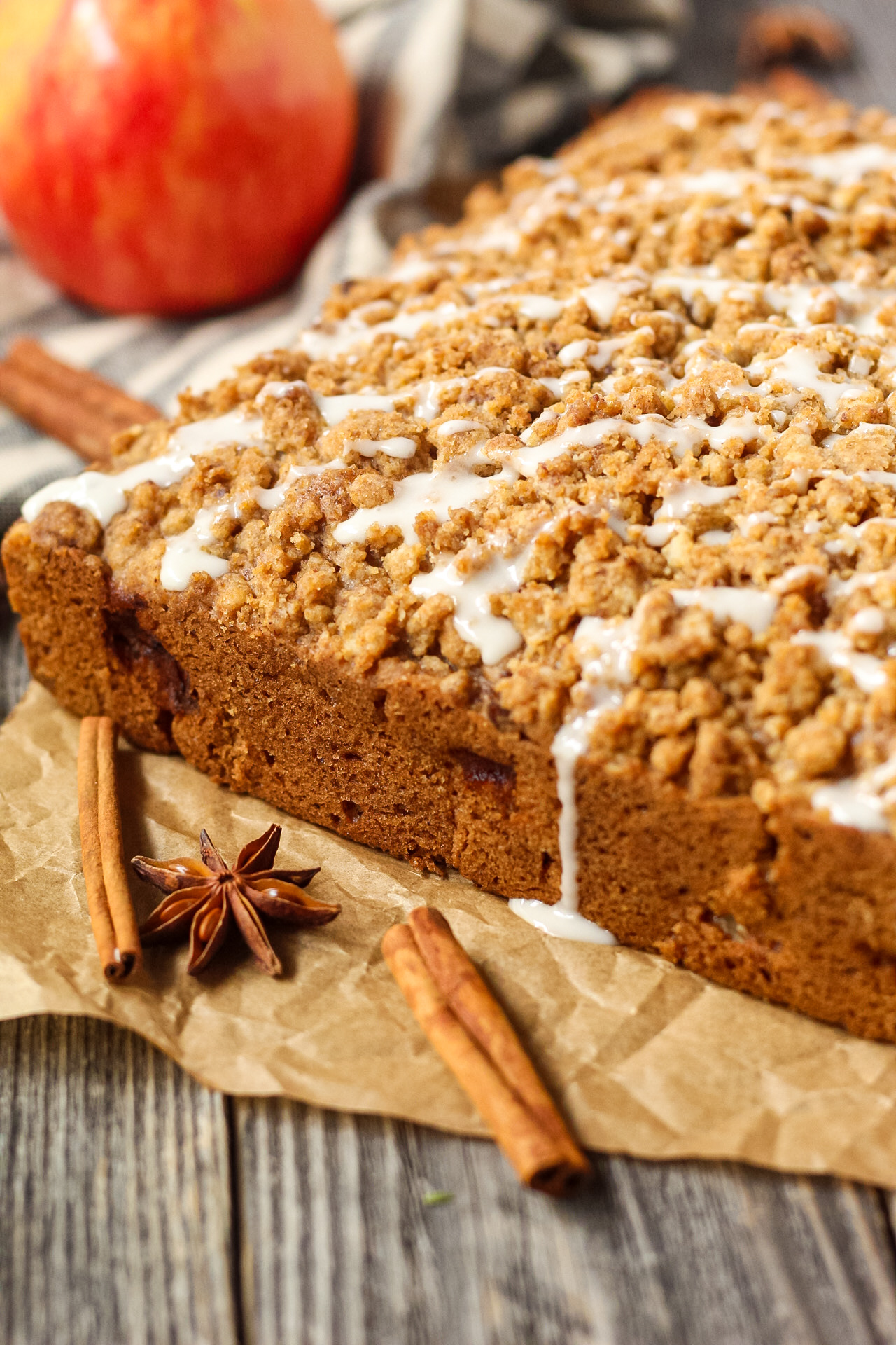 side shot of spiced apple crumb cake on wooden suface wiht an apple in the background.