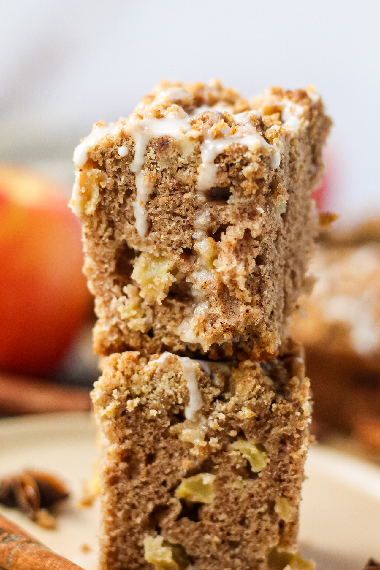 close up side shot of two slices of spiced apple crumb cake stacked on a brown plate with apples, cinnamon stick and star anise pods in the perimeter of shot.