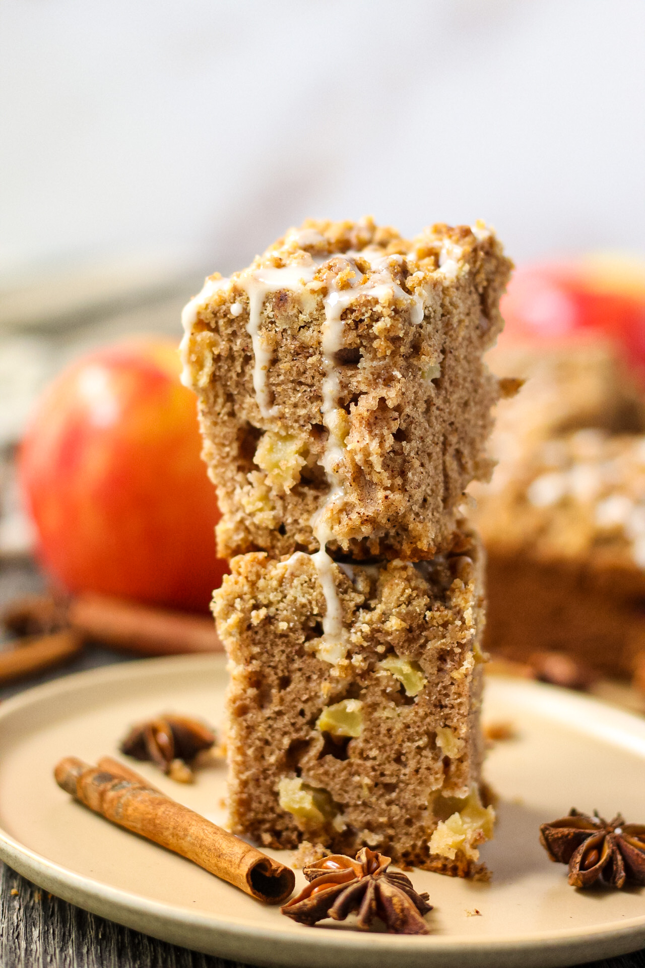side shot of two slices of spiced apple crumb cake stacked on a brown plate with apples, cinnamon stick and star anise pods in the perimeter of shot.