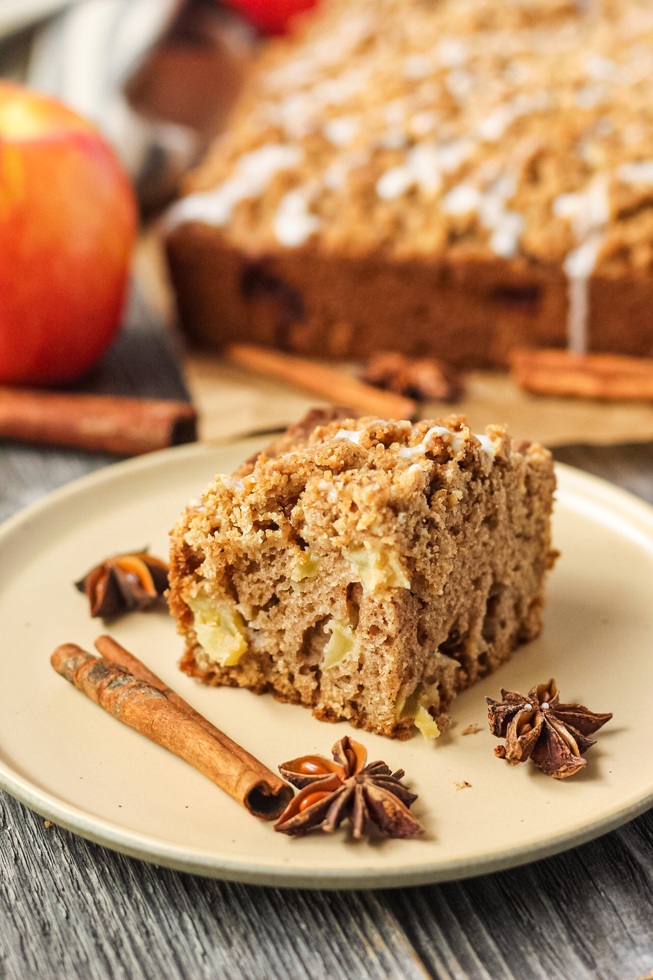 side shot of slice of apple crumb cake on a brown plate with apples and more cake in the background.