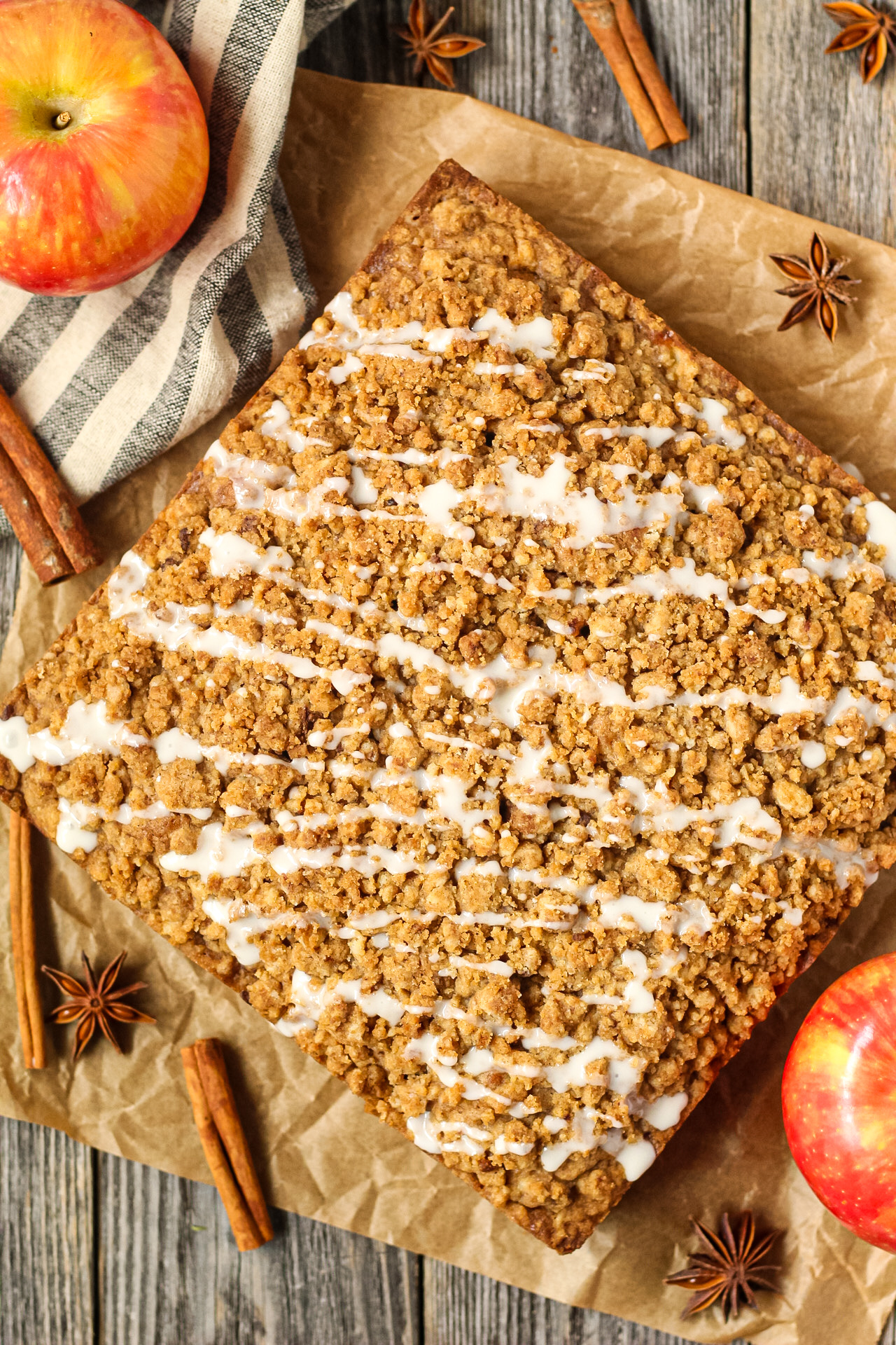 overhead shot of spiced apple crumb cake on parchment paper on top of wooden surface with apples and cinnamon sticks in the perimeter of the shot.