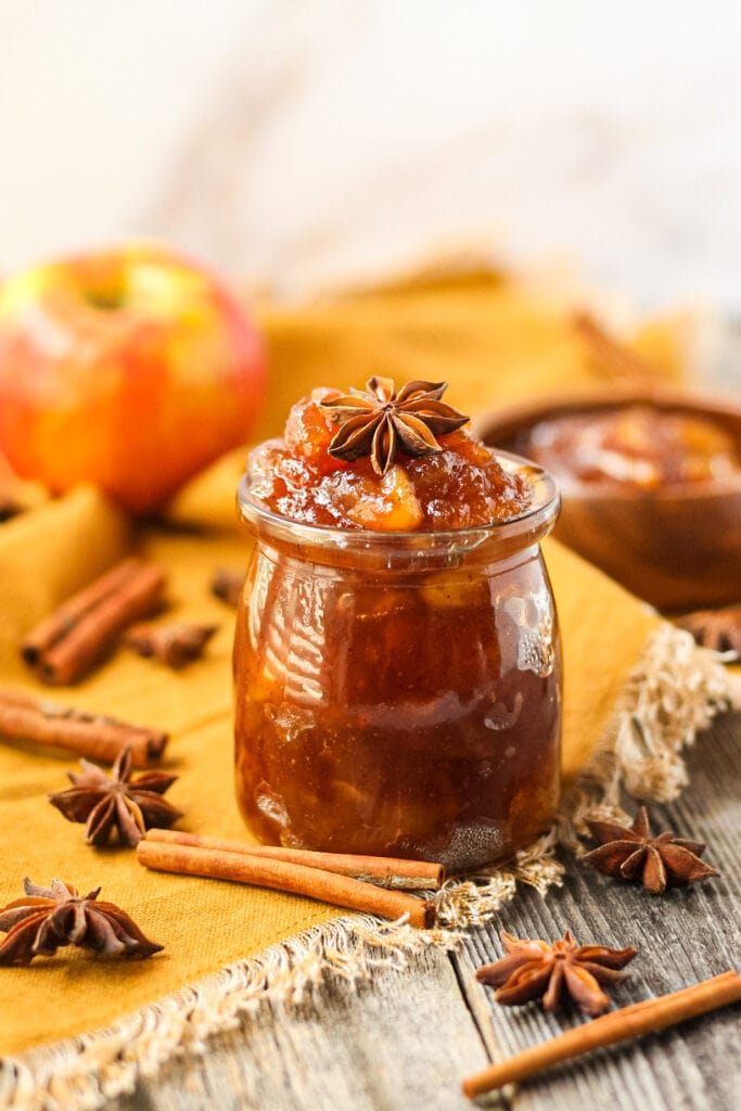 side angle shot of spiced apple jam in a glass jar with a orange linen underneath. cinnamon sticks and star anise in perimeter of shot.