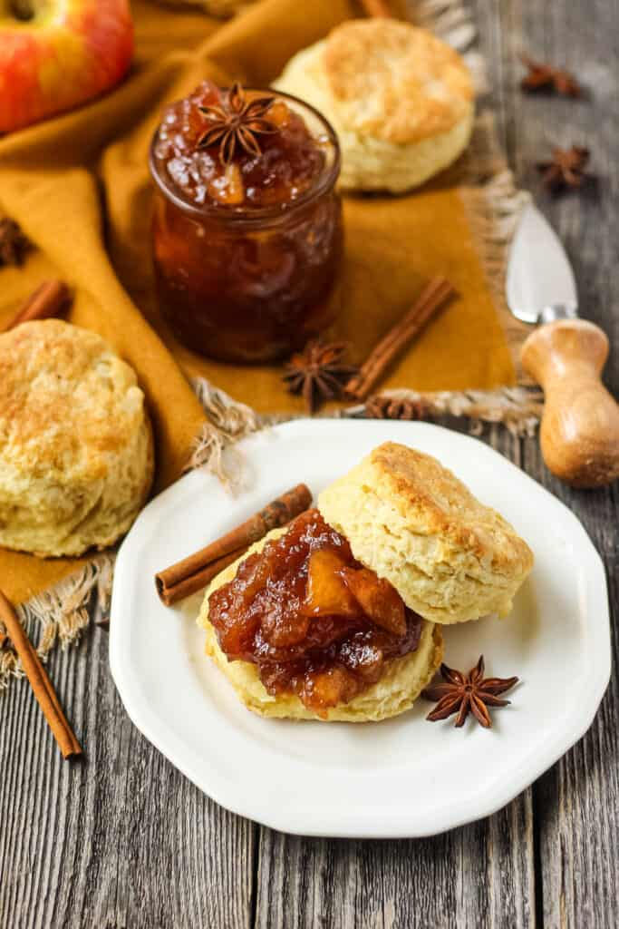 overhead shot of buttermilk biscuit sliced on a plate with spiced apple jam spread on biscuit. Plate is on a wooden surface with an orange linen underneath.