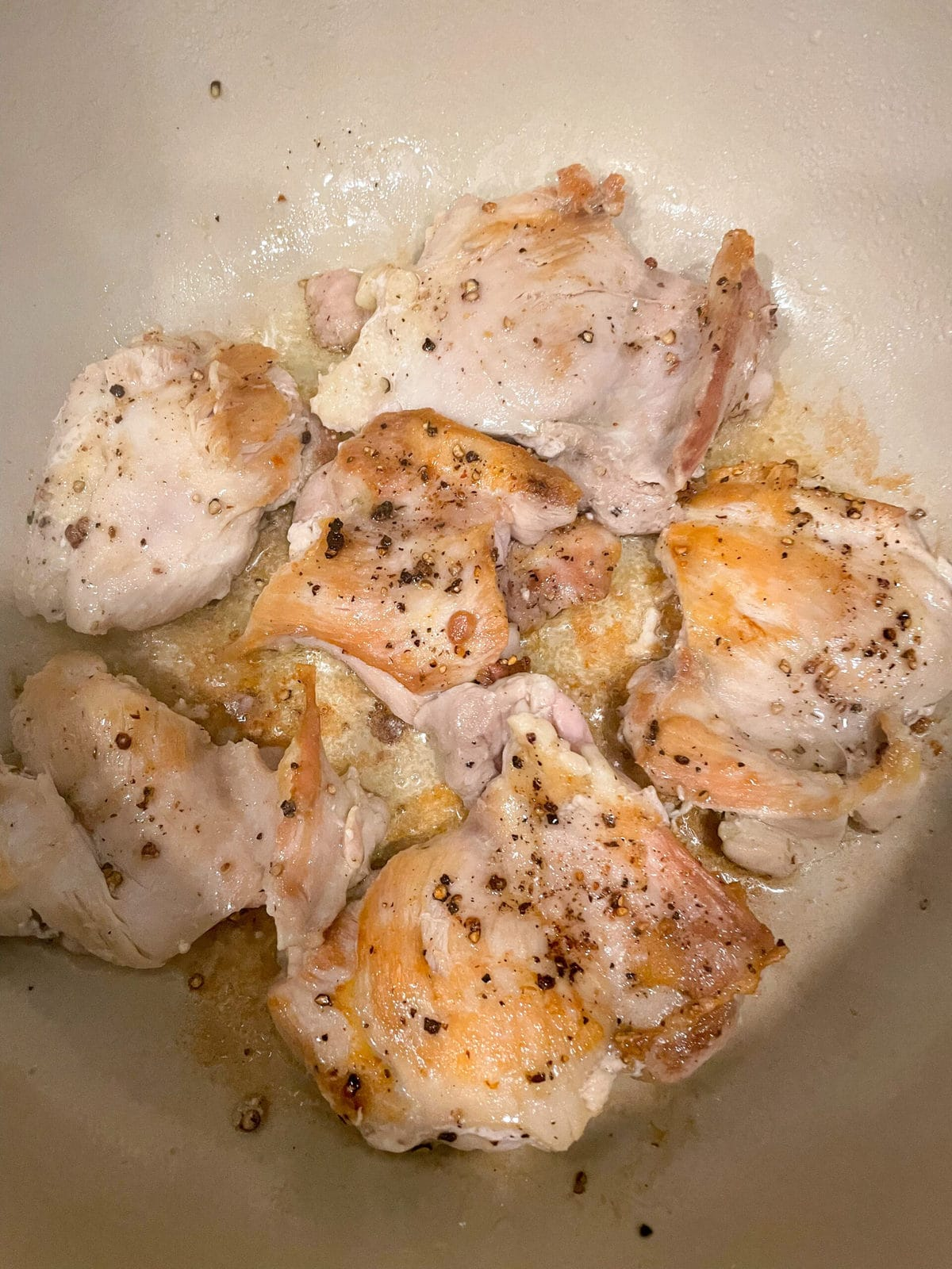overhead shot of seared chicken thighs in dutch oven