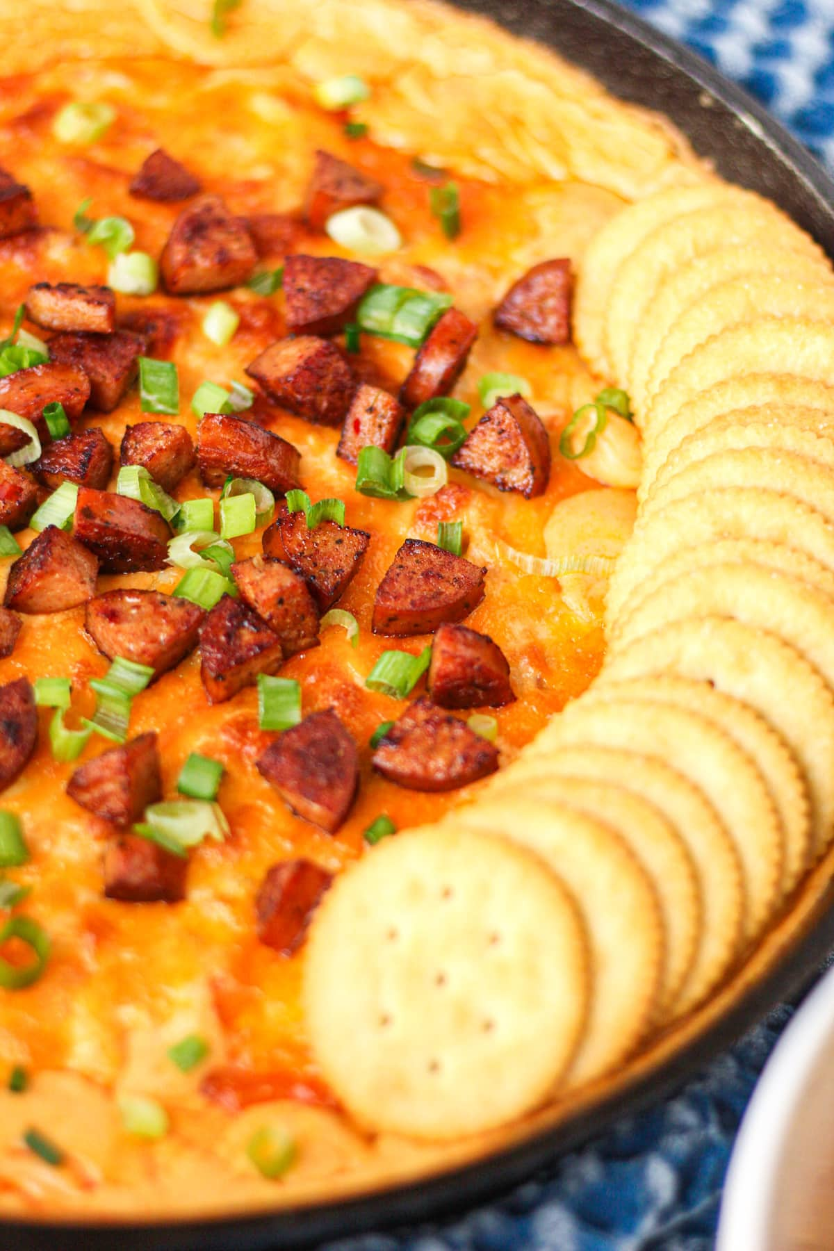 close up side angle shotof cheesy cajun chicken and sausage dip in cast iron skillet with blue towel underneath.