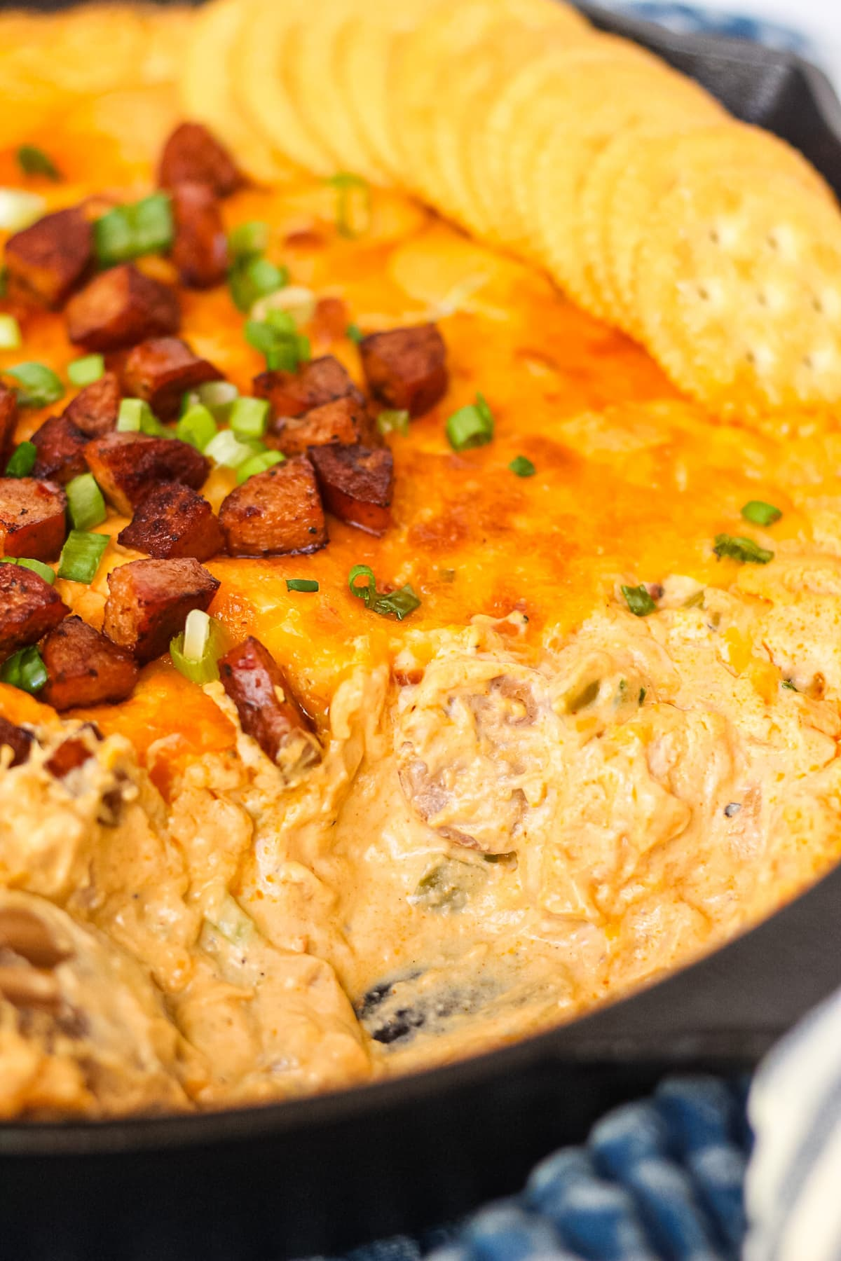 close up side angle shotof cheesy cajun chicken and sausage dip in cast iron skillet with blue towel underneath. serving of dip has been scooped out of skillet.